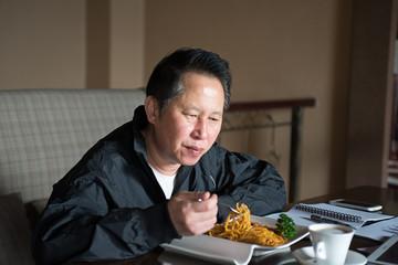 Middle-aged man eating noodles
