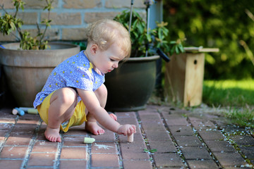 Cute toddler girl plays outdoors drawing with chalk
