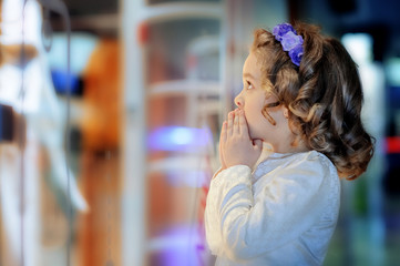 Little cute girl looking at shop window in the mall.