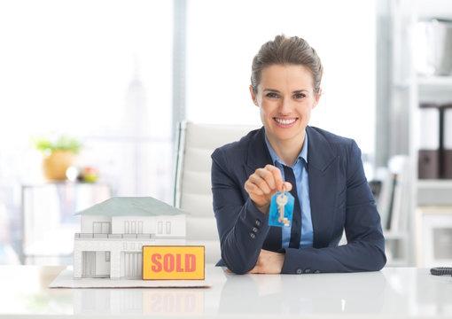 Happy realtor woman showing keys
