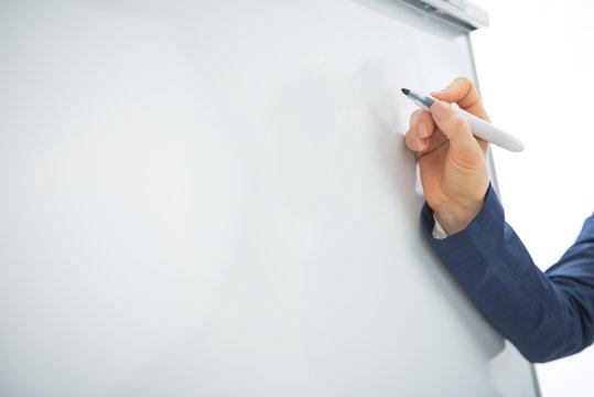 Closeup on business woman writing on flipchart
