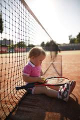 little girl plays tennis