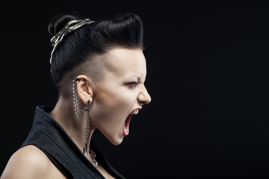 angry young woman screaming isolated on black background with co