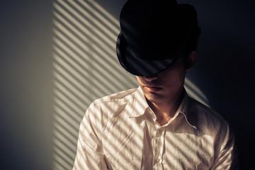 Man in hat next to window
