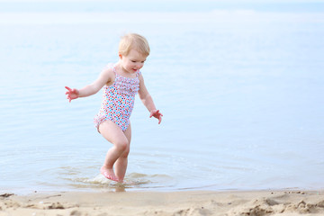 Cute toddler girl in colorful spotty swimsuit playing on beach