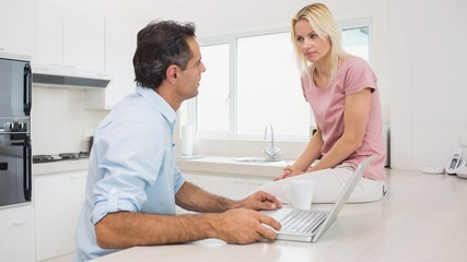 Serious couple with laptop sitting in kitchen