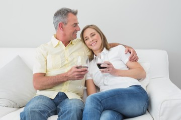 Couple with wine glasses sitting on sofa