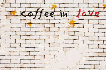 """""""coffee in love"""" layered on a brick wall"""