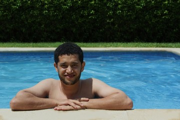 Young moroccan man smiling in swimmming-pool