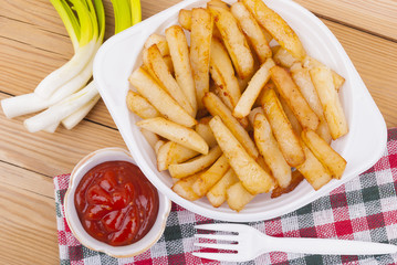 French fries with ketchup and onions on a wooden table.