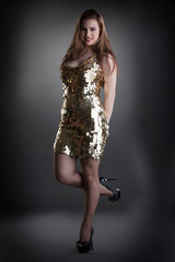 Seductive young girl posing in shiny golden dress