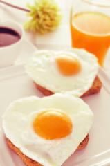 heart-shaped fried eggs, bread and orange juice