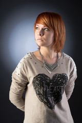 Young redhaired woman. Studio shot. Heart.