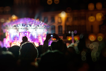 Man photographing with smartphone during a public concert