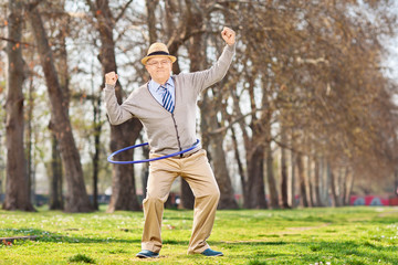 Senior man, exercise with a hula hoop in park