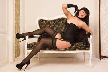 Pin-up girl wearing black underwear posing on the couch