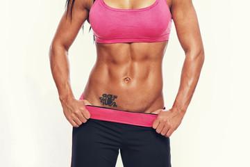 Close portrait of muscle woman body in studio