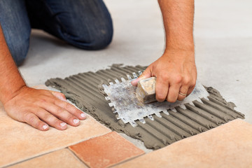 Worker hands spreading adhesive for ceramic floor tiles