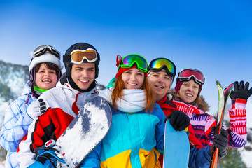 Five positive friends with snowboards