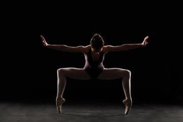 Silhouette ballet dancer in black swimsuit