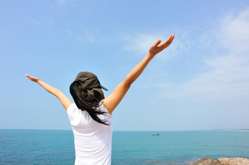 cheering woman open arms at  seaside