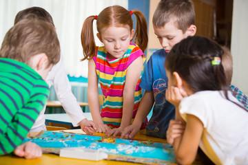 Cute preschoolers plaing game on table