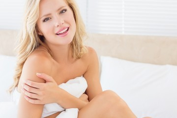 Sexy smiling young blonde covering herself with sheet