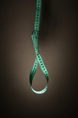 Tape measure noose on grey background - diet concept