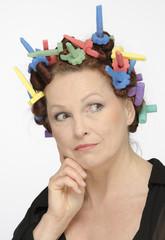 Reife Frau mit Lockenwicklern geschminkt nachdenklich