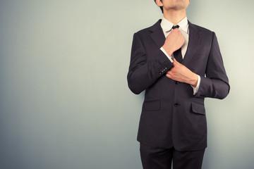 Young businessman adjusting his tie