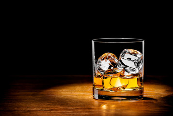 Wall Mural - whiskey with ice on a wooden table
