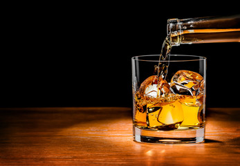 Fototapete - Pouring whiskey drink into glass