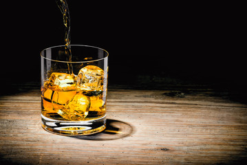 Fototapete - whiskey with ice on a wooden table