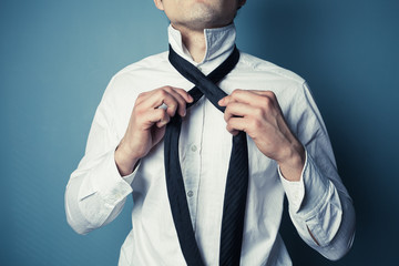 Young man tying his tie