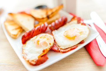 close-up of healthy breakfast with fried eggs, bacon, sausages