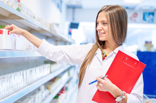 blonde pharmacist picking medicine and drugs from shelves