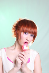 cheerful girl with lollipop in shape of heart on light backgroun