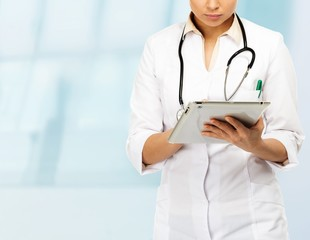 Young brunette doctor woman taking notes on tablet pc