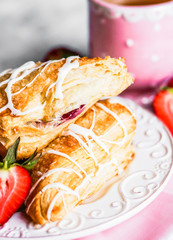 Fresh croissants with strawberries on wooden background