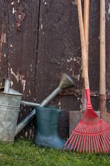 Gartenwerkzeug vor alter Gartentür