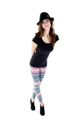 female model wearing heels, cut hat and colorful leggings