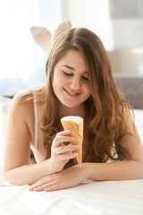 girl lying on bed and looking at ice cream cone