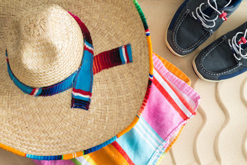 Sombrero, beach towel and sneakers on sand