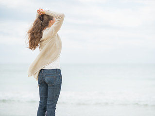 Young woman on cold beach looking into distance