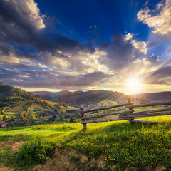 wooden fence in the grass on the hillside at sunset