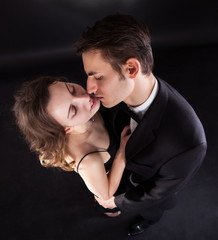 Passionate Couple Kissing Over Black Background