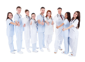 Group of cheerful doctors showing thumbs up