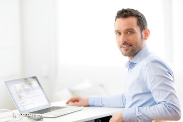 Young business man working at home on his laptop