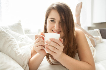 smiling woman drinking coffee in bed at morning