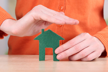Little paper house in hand close-up, on light background